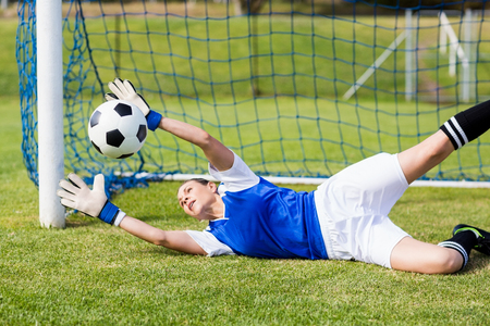 athleticism: Female goalkeeper saving a goal during a game Stock Photo