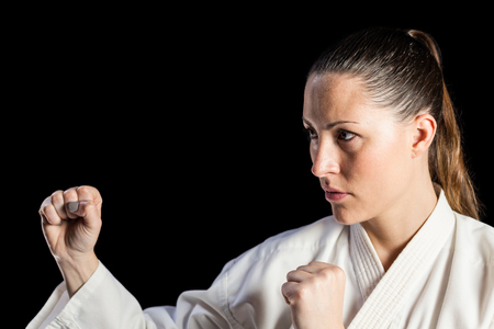 karateka: Female fighter performing karate stance on black background