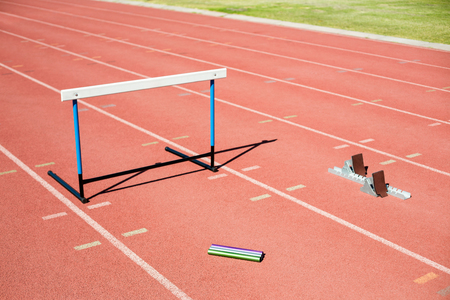 relay baton: Hurdle, relay baton and a starting block kept on a running track in stadium
