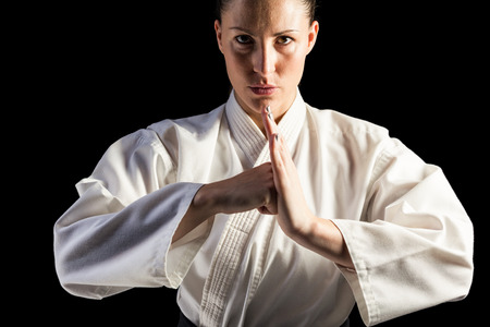 female fighter: Portrait of female fighter performing hand salute on black background Stock Photo