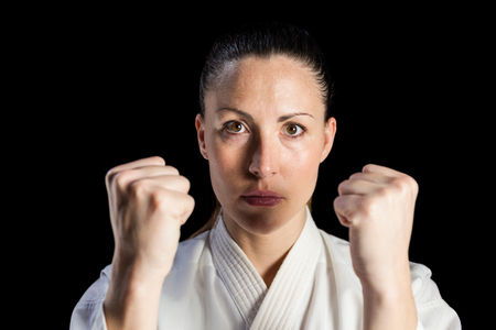 punched out: Portrait of female fighter performing karate stance on black background Stock Photo