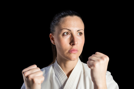 female fighter: Female fighter performing karate stance on black background