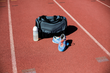 athleticism: Sports bag, shoes and a water bottle kept on a running track in stadium