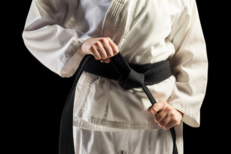 tightening: Mid section of fighter tightening karate belt on black background