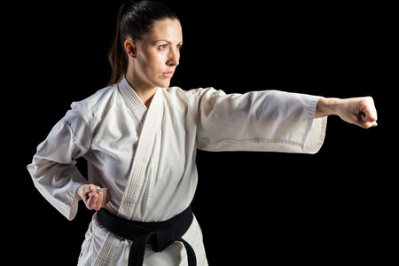 punched out: Female fighter performing karate stance on black background