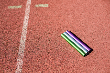 carrera de relevos: La batuta de relé en pista de atletismo en el estadio