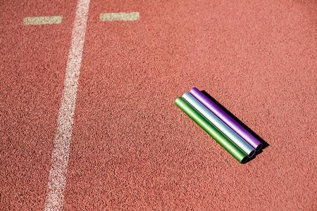 athleticism: Relay baton on running track in stadium