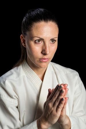 karateka: Close-up of karate fighter meditating on black background Stock Photo