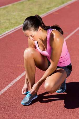 pista de atletismo: Female athlete tying her running shoes on running track Foto de archivo