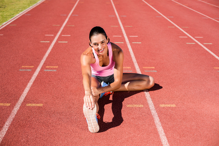 hamstring: Portrait of female athlete stretching her hamstring on running track Stock Photo