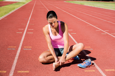 athleticism: Female athlete with foot pain on running track on a sunny day