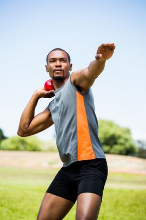 lanzamiento de bala: atleta masculino a punto de tirar tiro bola puesta en estadio