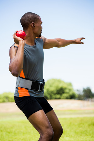 put: Male athlete about to throw shot put ball in stadium Stock Photo