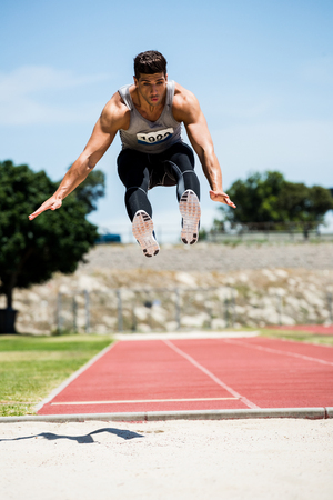 male athlete: Athlete performing a long jump during a competition