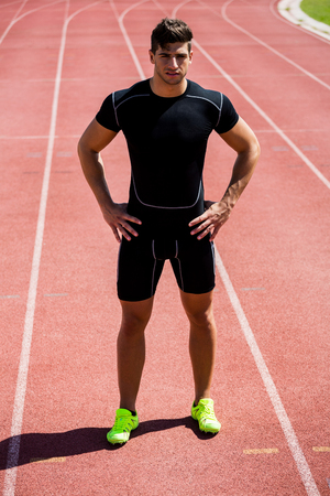 athleticism: Athlete standing with hand on hip on running track