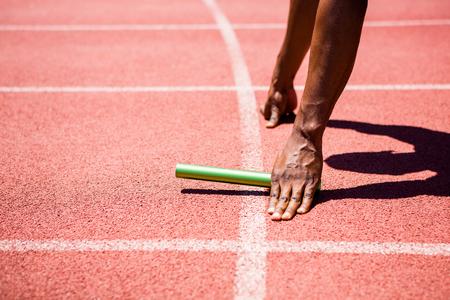 Handen van atleet met baton op renbaan