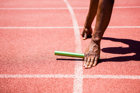 Hands of athlete holding baton on running track Stock Photo