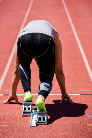 starting block: Rear view of determined athlete on a starting block about to run Stock Photo
