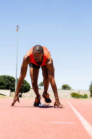 starting block: Determined athlete on a starting block about to run