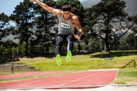 salto de longitud: Atleta realización de un salto de longitud durante una competición
