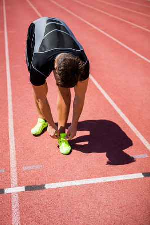 shoe laces: Male athlete tying his shoe laces on running track on a sunny day Stock Photo