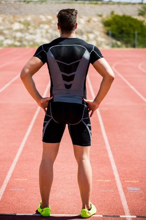 athleticism: Rear view of athlete standing with hands on hip on running track Stock Photo