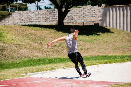 athleticism: Rear view of athlete performing a long jump during a competition