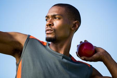 shot put: Primer plano de atleta decidido a punto de lanzar lanzamiento de peso bola