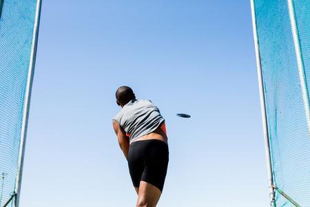 discus: Rear view of athlete throwing discus in stadium