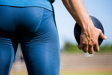 discus: Mid section of athlete holding a discus in stadium Stock Photo