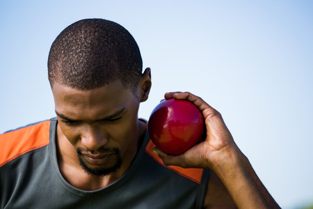 lanzamiento de bala: Close-up of male athlete holding shot put ball in stadium