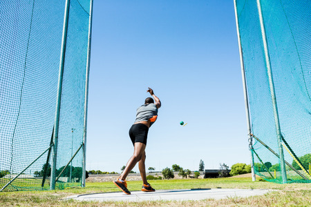 hammer throw: Determined athlete performing a hammer throw in stadium Stock Photo