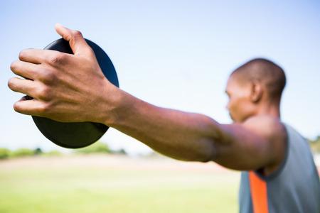 athleticism: Close-up of athlete holding a discus in stadium