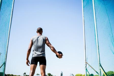 lanzamiento de disco: Rear view of athlete about to throw a discus in stadium Foto de archivo