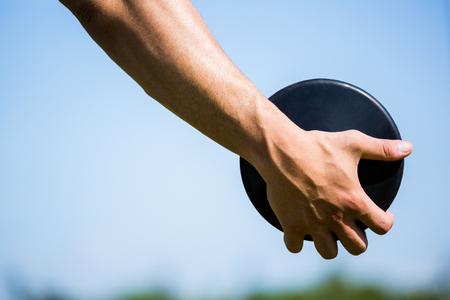 athleticism: Close-up of hand holding a discus in stadium Stock Photo