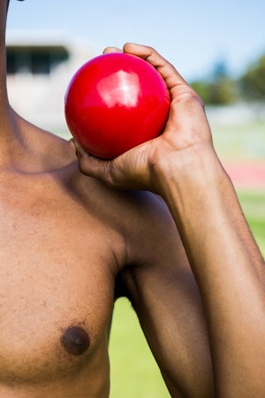 athleticism: Mid section of male athlete holding short put ball in a stadium Stock Photo