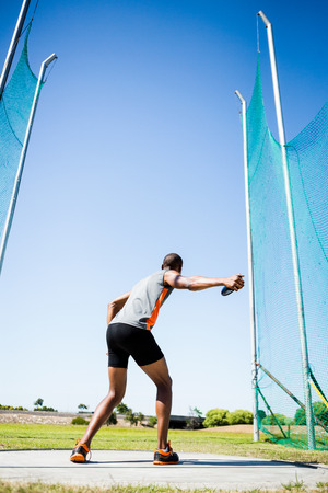 discus: Rear view of athlete about to throw a discus in stadium Stock Photo