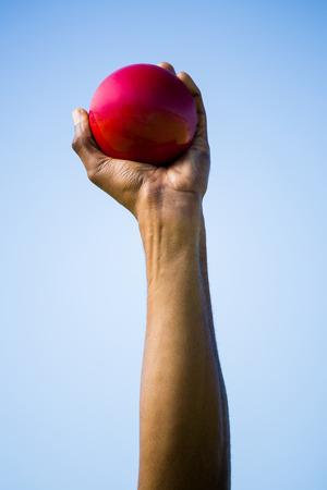 shot put: Athletes hand holding shot put ball on a sunny day