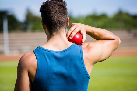 shot put: Rear view of male athlete about to throw shot put ball in stadium