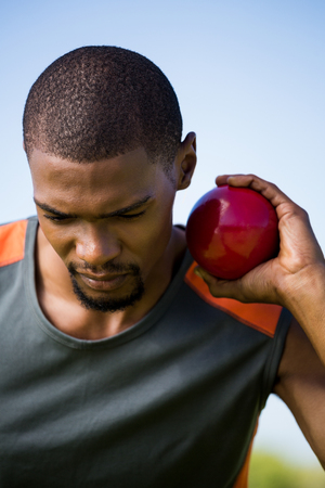shot put: Close-up of male athlete holding shot put ball in stadium
