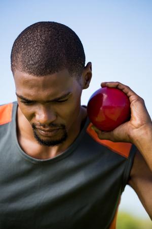 lanzamiento de bala: Primer plano de atleta masculino que sostiene lanzamiento de bala pelota en el estadio