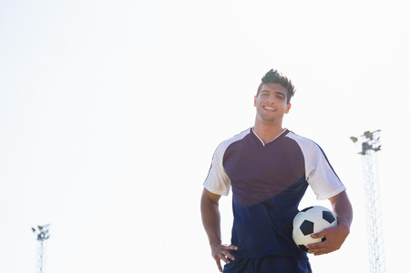 athleticism: Happy soccer player standing in stadium with a ball