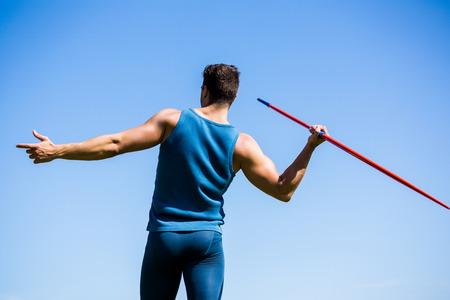 lanzamiento de jabalina: Vista trasera de un atleta a punto de lanzar una jabalina en el estadio Foto de archivo