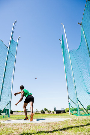 discus: Rear view of athlete throwing discus in stadium during competition Stock Photo