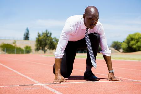 pista de atletismo: El hombre de negocios listo para correr en pista de atletismo