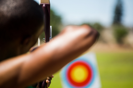 aiming: Close-up of athlete practicing archery in stadium Stock Photo