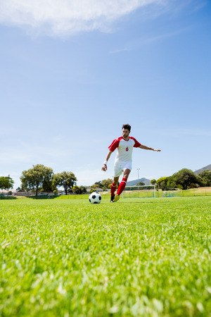 athleticism: Football player practicing soccer in a stadium