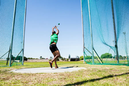 hammer throw: Rear view of athlete performing a hammer throw in stadium