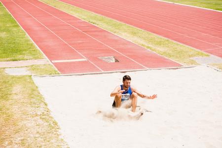 salto de longitud: aterrizaje atleta en arenero después de realizar una salto de longitud