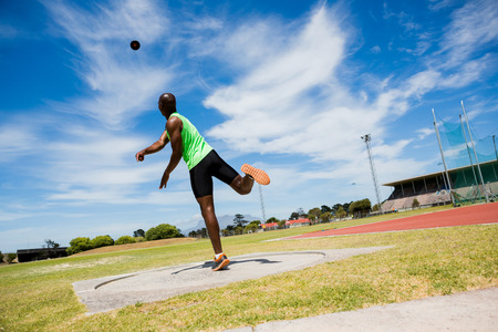 Male athlete throwing shot put ball in stadium Banque d'images